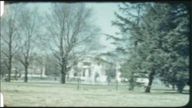 1940s: UNITED STATES: man on bike talks to lady with camera. View of building through trees.
