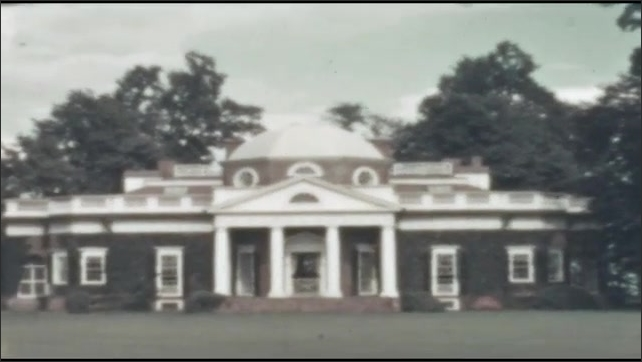 1940s: Monticello stands on lawn in national park. Trees and mountain view.  Car drives past hedge garden archway.