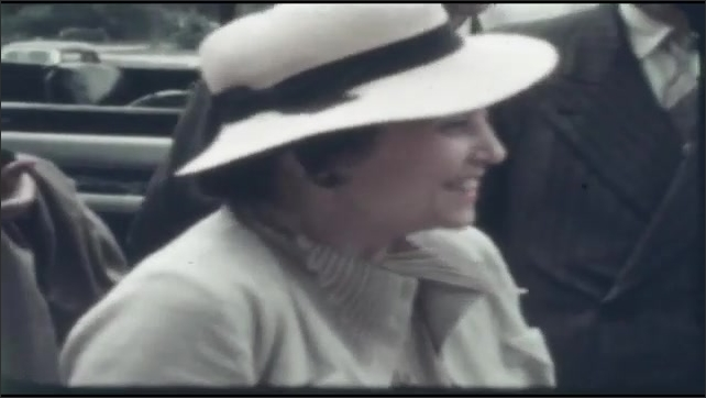 1940s: UNITED STATES: lady in hat smiles at camera. Long car and people waiting to ride. People gathered by stretched car.