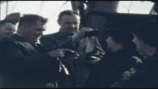 1940s: People talk and laugh on ship's deck.  Men hold devices.