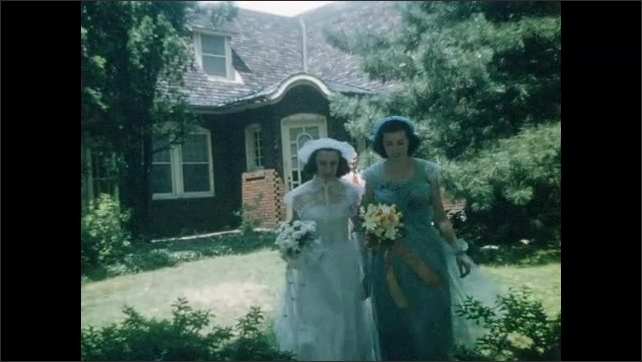 1940s: UNITED STATES: Bride and bridesmaid walk along garden path. Bride's family wait by car