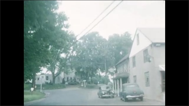 1940s: UNITED STATES: view along road from car windscreen. Trees by road. Child pushes bike on road. Car waits at corner of road