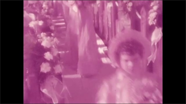 1940s: Bridesmaids, groomsmen, and flower girl walk down the aisle.