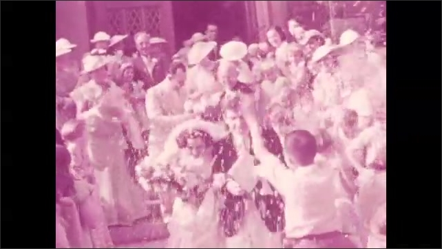1940s: Wedding guests exit church. Bride and groom exit church, guests throw confetti onto bride and groom. People linger on lawn outside church.