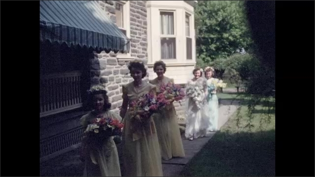 1940s: Wedding party lines up outside of house on sidewalk and begin walking. Three bridesmaids in yellow, the Bride and a Maid of Honor follows carries the veil.