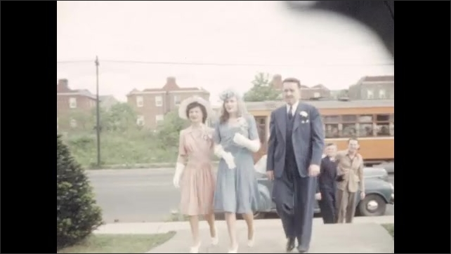 1940s: Wedding guests approach and enter the church. A streetcar goes by. Bride in blue suit enters church with parents. Bride and her father walk down the church aisle.
