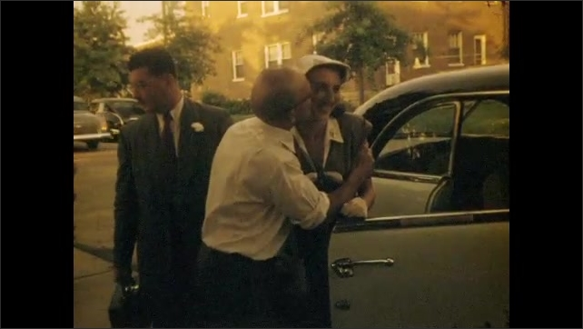 1940s: UNITED STATES: car outside garage. Guests at wedding. Man kisses lady on cheek. Bride and groom leave reception for honeymoon