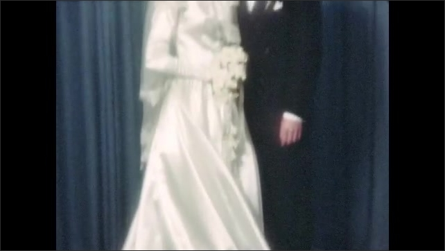 1940s: UNITED STATES: couple pose for wedding photos. Bride and groom have photos taken