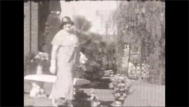 1930s: Woman exits house, walks past camera.
