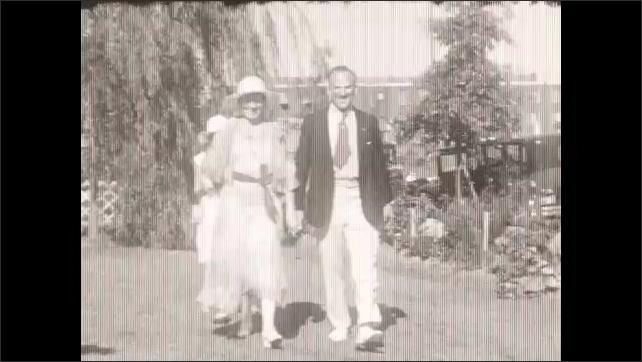 1930s: Man, woman and girl walk toward camera, man ducks under camera.