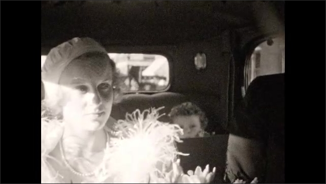 1940s: Woman, bride, girl, man sit inside car. Sun shines on woman????s face, bride smiles, man talks. Man stands next to parked car, subway passes by on elevated track, crowd stands on sidewalk.