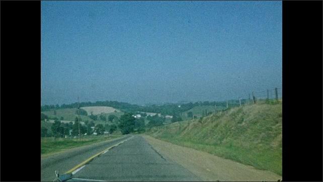 1940s: Car drives down highway.  Farmland.