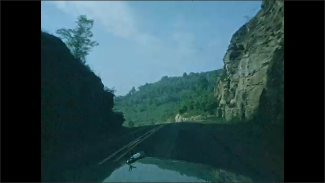1940s: Car drives down road.  Mountains.