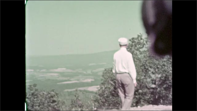 1930s: Man walks across plateau, waves. Cars parked at overlook.