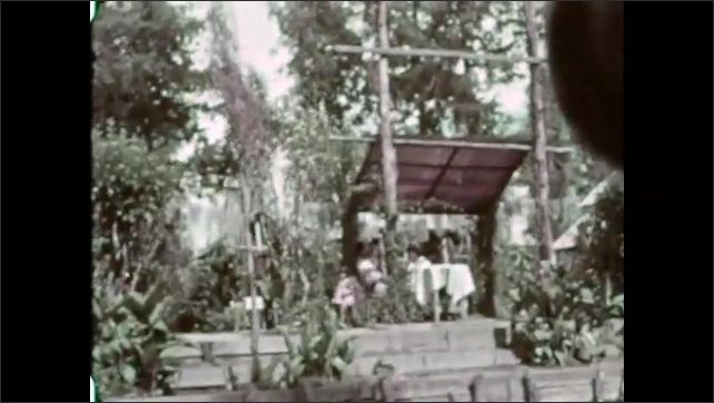 Mexico 1930s: Woman paddles by on canoe. Woman on boat smiles. Boats pass. Buildings/village on edge of river. Bridge of river. Trees and bushes on edge of river.
