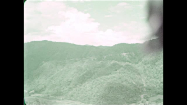 1930s: Three women lean against stone, talk. Valley and mountains. Man and women lean against stone.