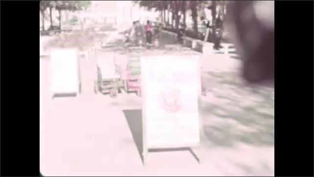 1930s: People hide behind sign, women walk around sign, man climbs under it. Man pretends to eat watermelon off sign. People walk through park.