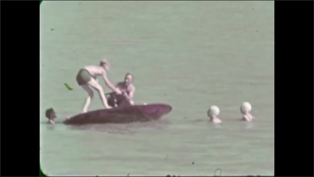 1930s: Women and men play and climb on spinning disc in water.