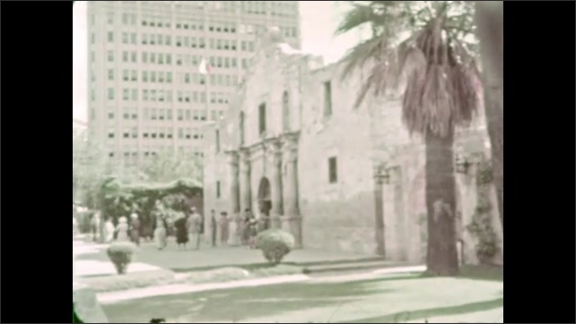 1930s: Well-dressed women walk out of stone building into afternoon sun. The women walk around garden courtyard.