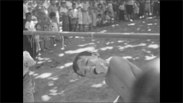 1930s: Boys race with hands behind back, try to eat food off string with their mouths only. People picnic on beach.