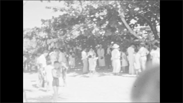 1930s: People play, walk, gather, picnic at beach.