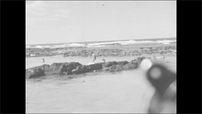 1930s: People swim in the ocean, stand on the beach.