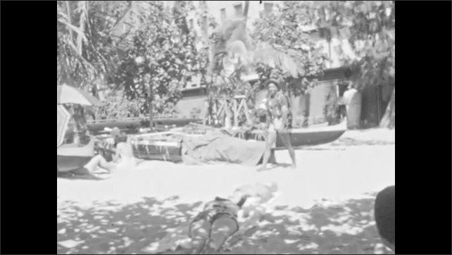 1930s: Men in swimming trunks walk by, people sunbathe in front of boats, umbrellas, palm trees. Man shimmies, dances, puts foot up on boat, smiles, laughs. Woman in bathing suit lies on towel.