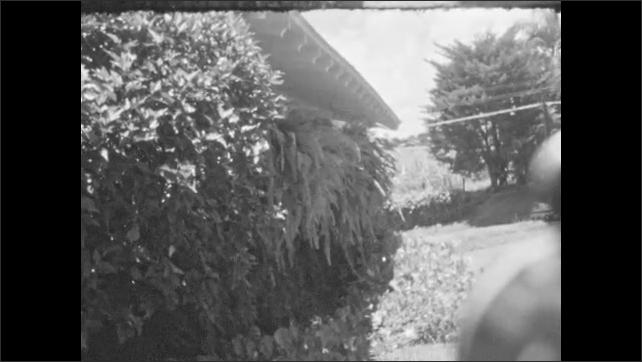 1930s: Descriptive text slide. House covered by plants. Women walk around house, woman picks flower.