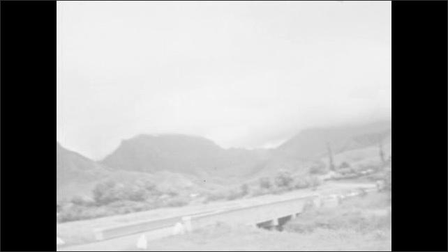 1930s: HAWAII: family walk outside house. Car parked by house. View from mountain road