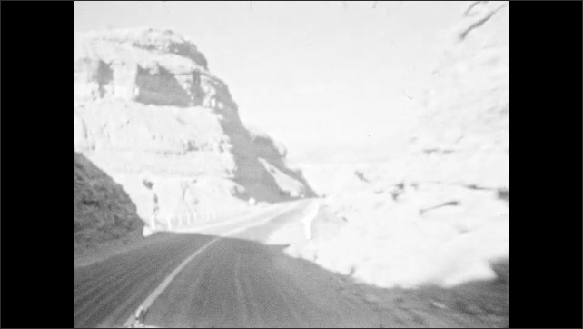 1930s: HAWAII: trees and shrubs by long road. Car drives through mountain landscape. Remote road through desert. Safety barriers by road