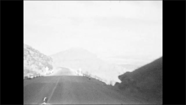 1930s: HAWAII: car drives along road. View through tunnel under rock. Train tracks on slope.