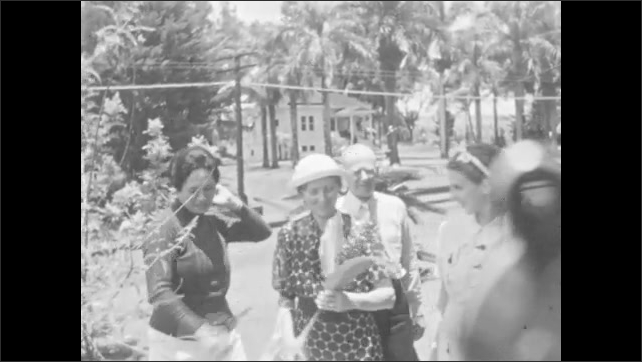 1930s: People walk around outside, woman holds large leaf. Man stands next to woman with his arm over her shoulder, man blows a kiss, woman talks.