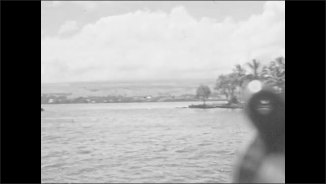 1930s: Ocean. Boat on water, person swims in water. Palm trees, clouds. Descriptive text slide.