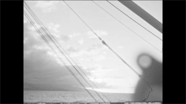 1930s: Ocean and boat deck. Sun shines through clouds.