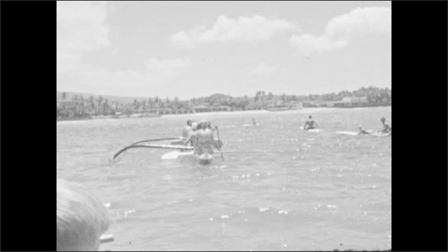 1930s: Outrigger canoe paddled on the ocean. Canoes on the water.