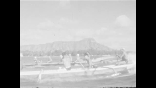 1930s: Outrigger canoes paddle and surf on the ocean and waves.