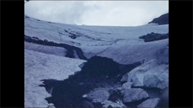 1950s: View of snow-capped mountain. Close-up of glacier.