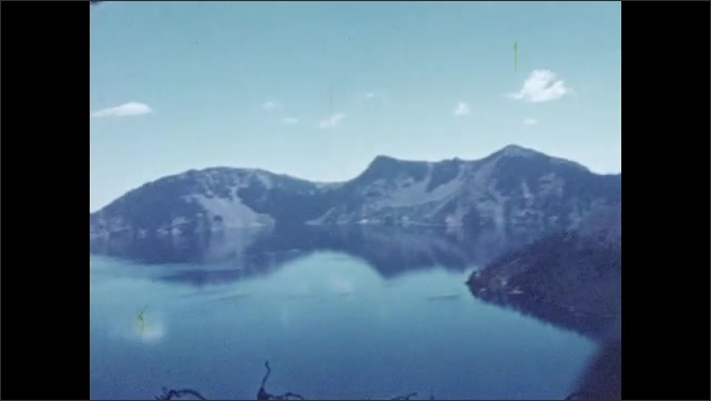 1950s: View of mountain with parking area and tree in foreground. Lake in mountain range with island.