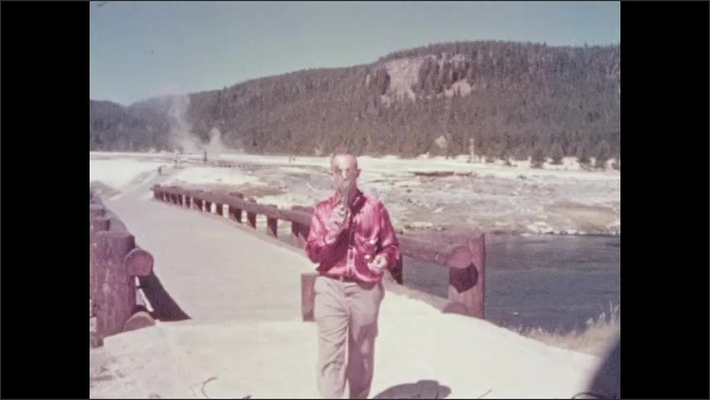 1950s: UNITED STATES: Close up of geyser pool. Man pulls object from geyser pool. Man walks towards camera. Mustard Springs sign.