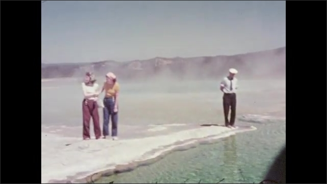 1950s: UNITED STATES: Fountain geyser sign. Man stands by pool. Water in pool. Visitors wave from site of geyser. View of trees in gorge