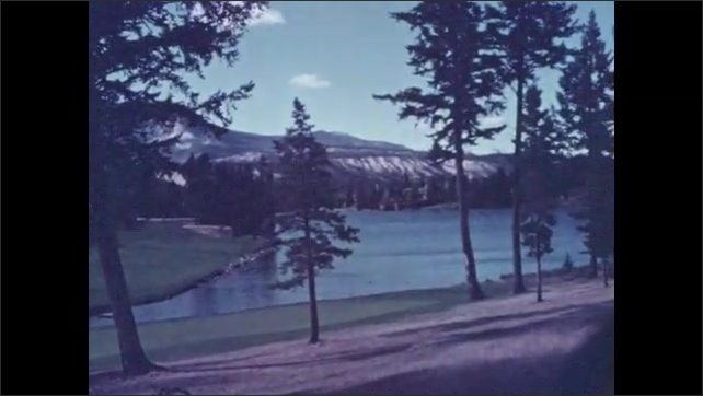 1950s: Tilt up bridge to mountain. High angle pan of river. Pan across lake. View of road and mountain.