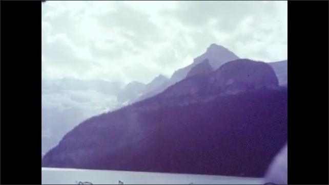 1950s: Long shot, horseback rider by lake, pan across lake. Pan across mountains, view of hotel. Pan across hotel.