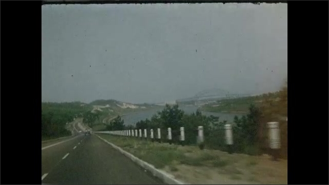 1950s: Grassy shore with water in distance. Large river runs through land with sail boat on it. Driving down road next to river. Driving towards bridge. Houses along beach. People sitting on beach.