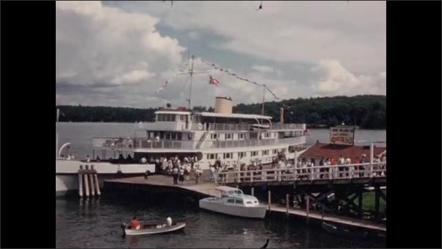 1950s: Lake, town. Boat at dock, people exit boat, walk up ramp. Bear on platform.