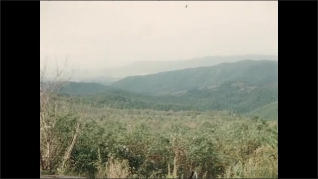 1950s: UNITED STATES: Lady walks past house. Ground water sign. View across trees in valley. Wall on edge of lookout