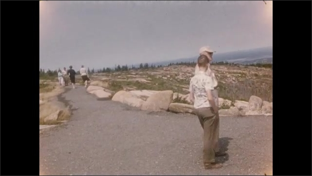 1950s: People walking along paths at hillside, scenic park. Driving down road.