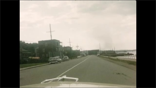 1950s: Car drives down road through town, along waterfront.