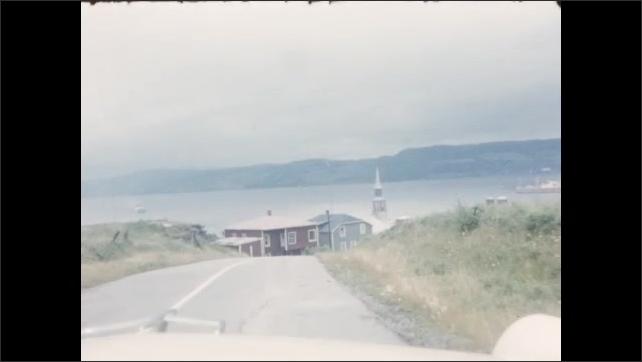 1950s: Car drives over bridge, car drives through country. Car drives along waterfront road.