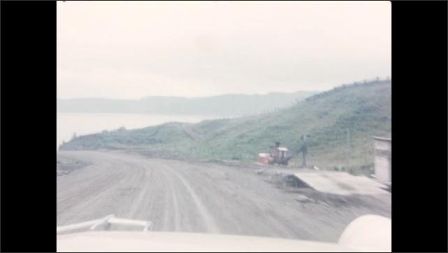 1950s: Car drives along waterfront road. Car drives along dirt road.