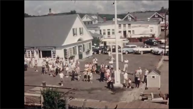 1950s: Lake, trees, town. Boat pulls into port. People wait at dock.